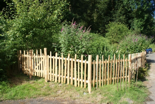 rustic cleft chestnut Staggered height picket fencing with wicket gate