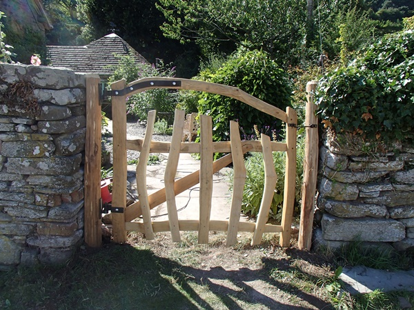 Cleft Chestnut gate with bent top rail and blacksmith forged furniture