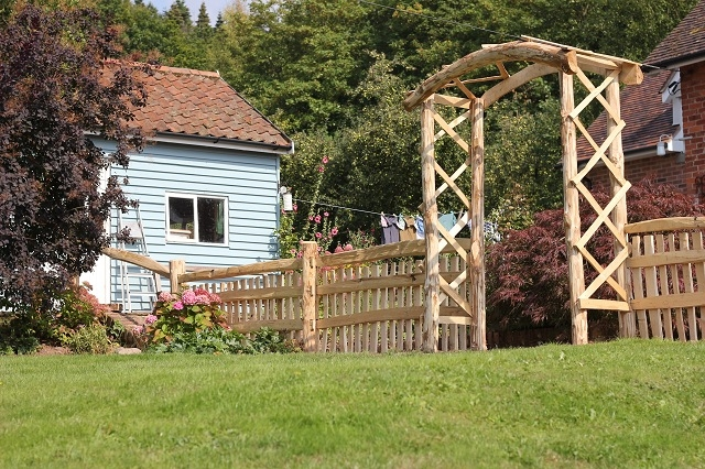 Mortise framed Cleft Chestnut picket fencing with handrail and rose arch