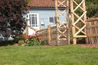 Mortise framed Cleft Chestnut picket fencing with handrail and rose arch in Herefordshire