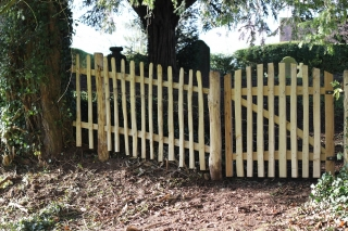 Avenbury gate and cleft picket fencing in a churchyard