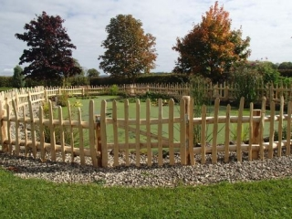 Rustic fencing Staggered height picket fencing with wicket gate