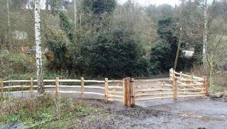 A pair of rustic cleft Chestnut Mordiford gates with post and rail fencing