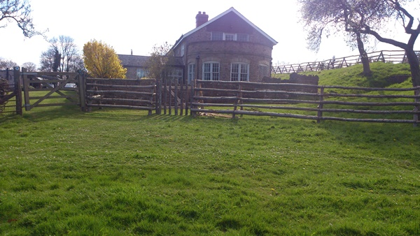 Free standing cleft Chestnut post and rail fence around a house with archaeological restrictions preventing digging