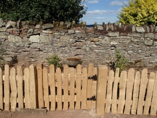 Close spaced rustic cleft oak picket fencing with Avenbury gate